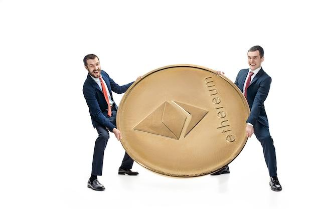 Twee zakenlieden die bedrijfspictogram houden - groot ethereum dat op witte achtergrond wordt geïsoleerd. cryptocurrency, bitcoun, litecoin, e-commerce, financieel concept. collage Gratis Foto