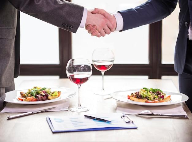 Twee zakenlieden die handen schudden tijdens een bedrijfslunch. Premium Foto