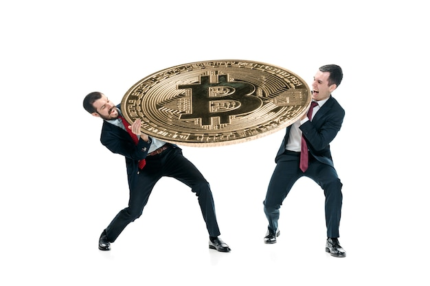 Twee zakenlieden die in kostuums bedrijfspictogram houden - grote bitcoin die op witte achtergrond wordt geïsoleerd. crypto-valutamunten, litecoin, ethereum, e-commerce, financieel concept. collage Gratis Foto