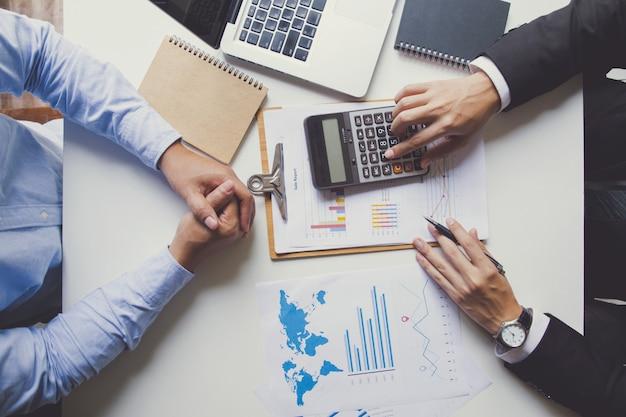 Twee zakenlieden die over in aanmerking komende investering spreken, manager die financieel rapport voorstelt dat goede werkresultaten toont aan tevreden baas Premium Foto