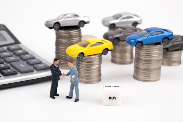 Twee zakenlieden en auto bovenop stapel muntstukken Premium Foto