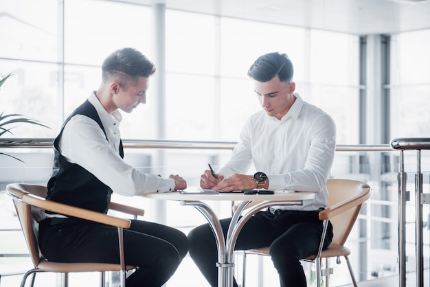 Twee zakenmensen ondertekenen documenten in een groot, ruim kantoor Gratis Foto