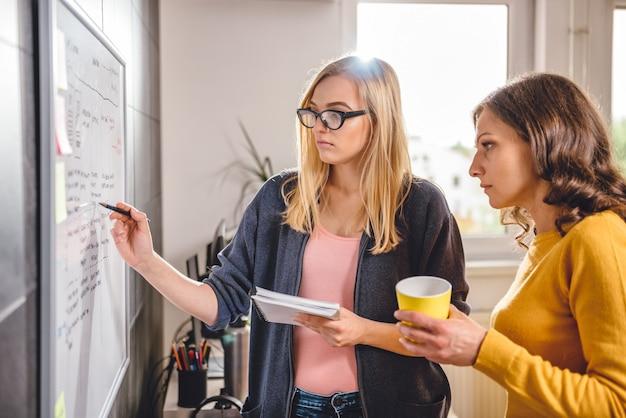 Twee zakenvrouw bespreken voor het whiteboard Premium Foto