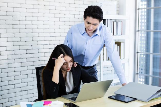 Twee zakenvrouw worden benadrukt op het werk met zaken man partners helpen bij het maken van positieve aanbevelingen werken met de computer op houten tafel en ideeën tijdens bijeenkomst op kantoor achtergrond. Premium Foto