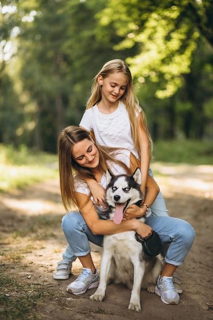 Twee zussen met hun hond in park Gratis Foto