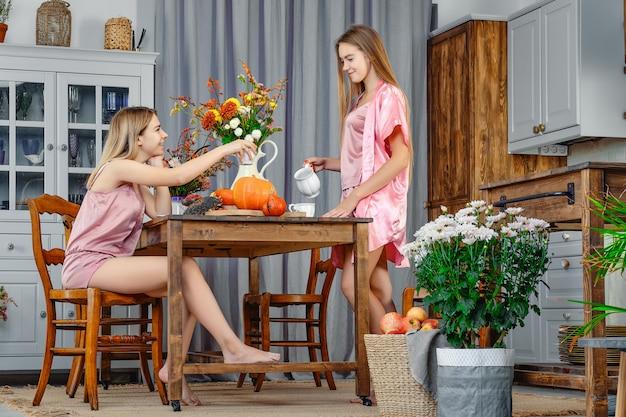 Twee zussen zitten voor elkaar in de keuken en praten Premium Foto