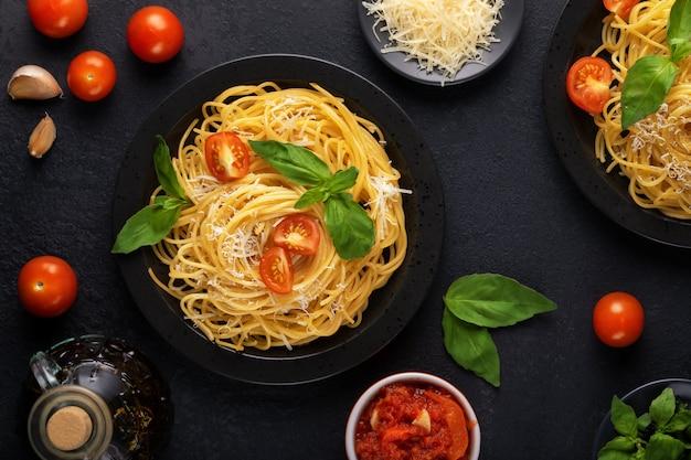 Twee zwarte borden met vegetarische smakelijke klassieke italiaanse spaghetti pasta met basilicum, tomatensaus, parmezaan en olijfolie op een donkere tafel. bovenaanzicht, horizontaal. Premium Foto