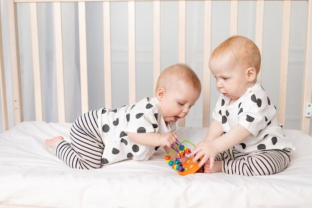 Tweelingbaby's spelen in de wieg, vroege ontwikkeling van kinderen tot een jaar Premium Foto