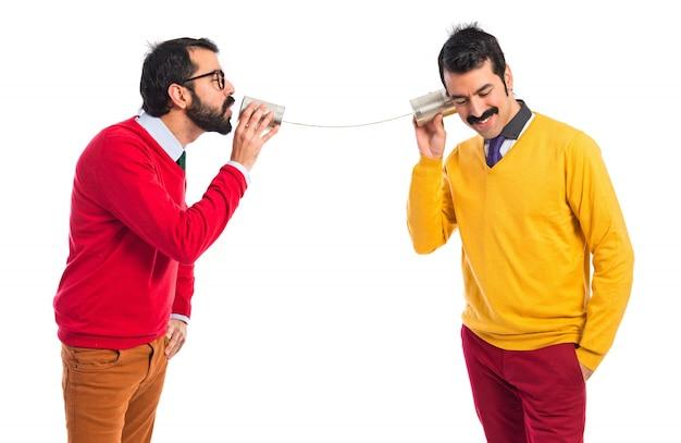 Tweelingbroers praten door een tin telefoon Gratis Foto
