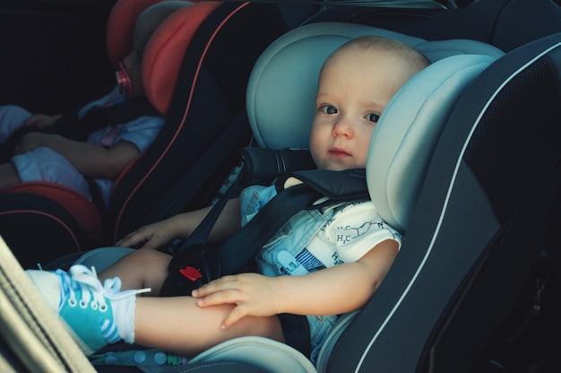 Tweelingenjongen en meisje in kinderzitjes in de auto. veiligheidsvervoer voor baby's. kinderen tot een jaar. Premium Foto