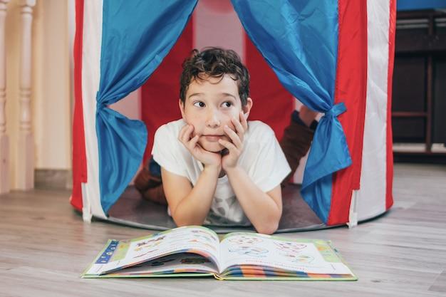 Tween denkende jongen met krullend haar in stuk speelgoed tenthuis die en boek thuis liggen lezen Premium Foto