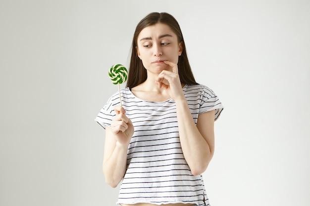 Twijfelachtig besluiteloos jonge europese donkerharige vrouw in vrijetijdskleding bijtende vinger als ze kijkt naar kleurrijke lolly in haar hand, aarzelt om het op te eten vanwege een gezond suikervrij dieet Gratis Foto