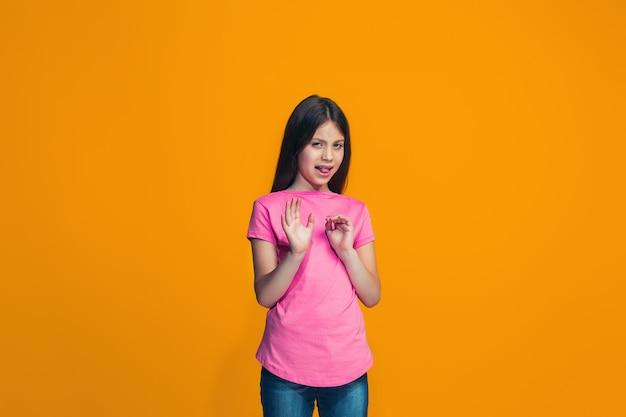 Twijfelachtig peinzend meisje dat iets verwerpt tegen oranje muur Gratis Foto