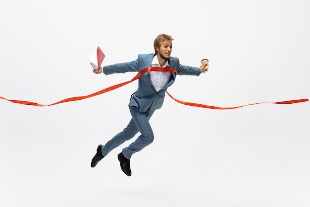 Typen. man in kantoor kleding lopen, joggen op witte ruimte zoals professionele atleet, sportman. ongewone look voor zakenman in beweging, actie met bal. sport, gezonde levensstijl, creativiteit. Gratis Foto