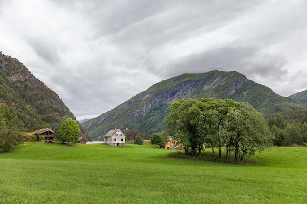 Typisch landschap noors landschap met huis. bewolkte zomerochtend in noorwegen, europa. Premium Foto