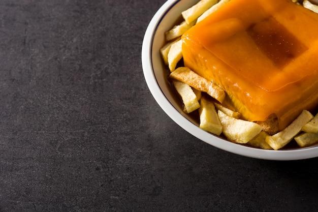 Typische portugese francesinha-sandwich met frieten op zwarte Premium Foto