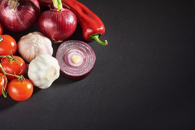 Ui en knoflook en hete pepers en tomaten geïsoleerd op een zwarte. Gratis Foto