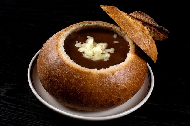 Uiensoep in zwart brood met geraspte kaas Gratis Foto