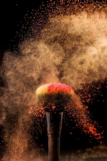 Uitbarsting van poeder en make-upborstel op donkere achtergrond Gratis Foto