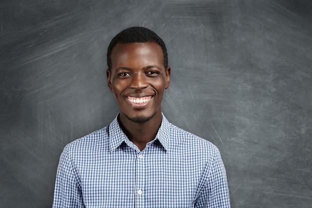 Uitdrukkingen, emoties en gevoelens van menselijke gezichten. portret van vrolijke afrikaanse werknemer lachend met zijn witte tanden, blij met grote promotie en carrièregroei. succes en prestaties. Gratis Foto