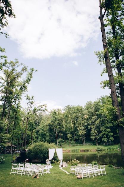Uitgaande huwelijksceremonie. decor studio. witte houten stoelen op een groen gazon. bruiloft feestelijke boog. witte fauteuils voor gasten Premium Foto