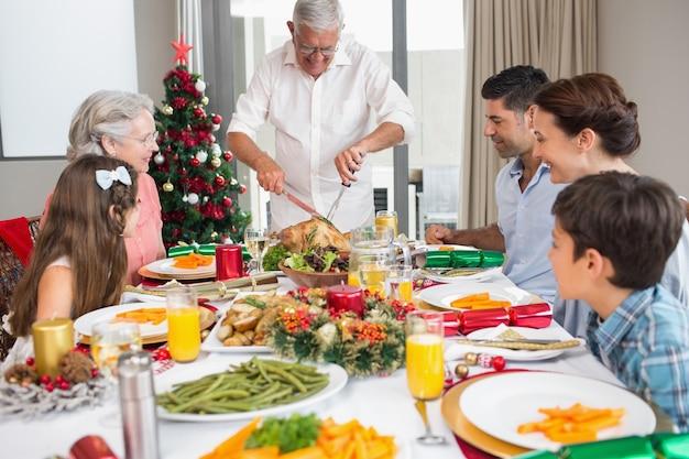 Uitgebreide familie aan eettafel voor kerstdiner Premium Foto