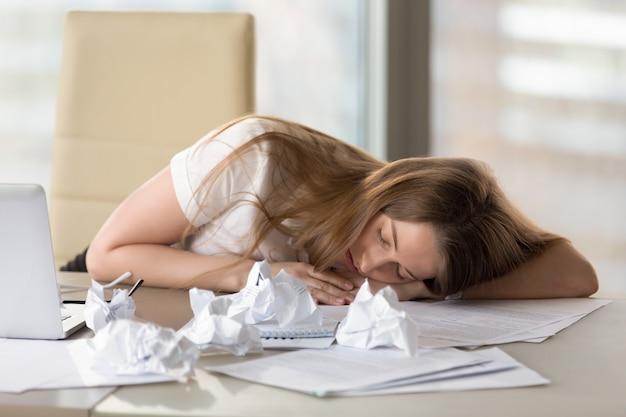 Uitgeput vermoeide vrouwenslaap bij bureau na overwerk in bureau Gratis Foto