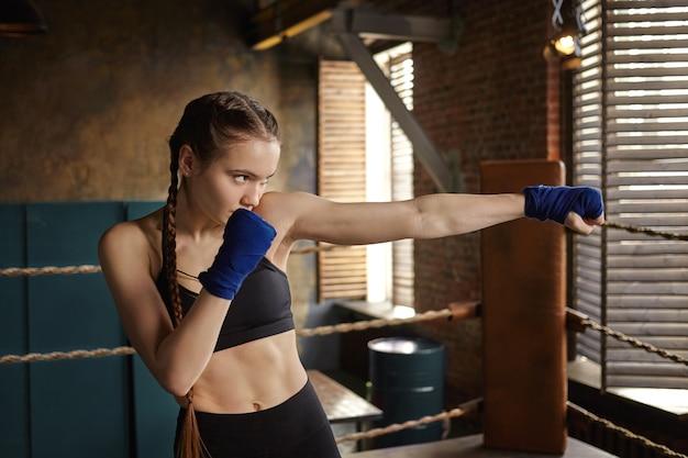 Uithoudingsvermogen, kracht, zelfverdediging en martial arts-concept. mooie vastberaden jonge vrouw kickbokser die binnenshuis traint, bezig met stoten Gratis Foto