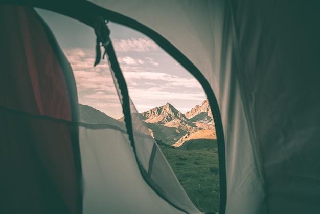 Uitkijkend op het berglandschap bij zonsopgang vanuit interieur van camping tent. Premium Foto