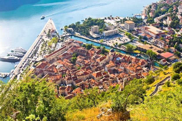 Uitkijkend over de baai van kotor in montenegro met uitzicht op bergen, boten en oude huizen met rode pannendaken Premium Foto