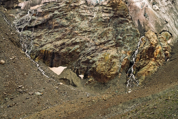 Uitlopers van gigantische gletsjer. verbazingwekkende rotsachtige reliëf met sneeuw en ijs. prachtige enorme berg rotsachtige natuurlijke muur met kleine watervallen. water uit gletsjer. fantastisch kunstwerk van majestueuze hooglandaard. Premium Foto