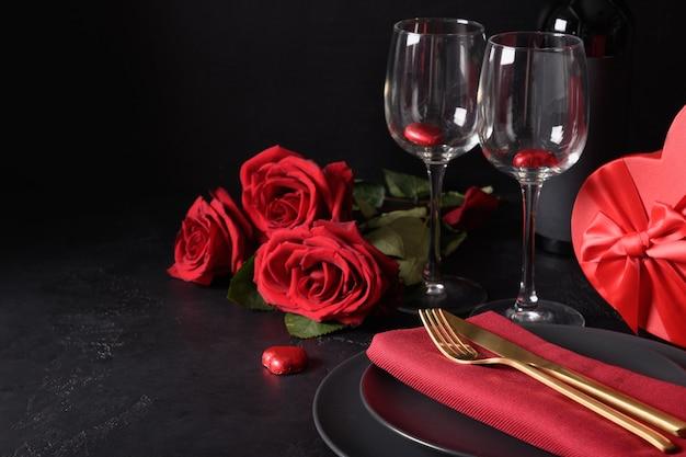 Uitnodiging voor valentijnsdagdiner. feestelijke tabel met romantisch cadeau, rode rozen op zwart. wenskaart met kopie ruimte. Premium Foto