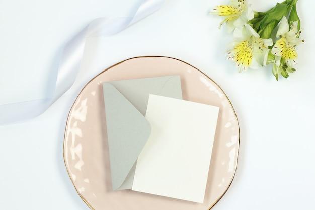 Uitnodigingskaart, bloemen, grijze envelop en lint op wit Premium Foto