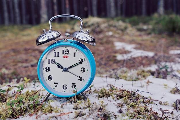 Uitstekende blauwe wekker op de winter bosachtergrond Premium Foto