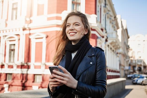 Uitstekende dag voor avonturen. stadsportret die van aantrekkelijke europese vrouw in straat lopen, die smartphone houden Gratis Foto
