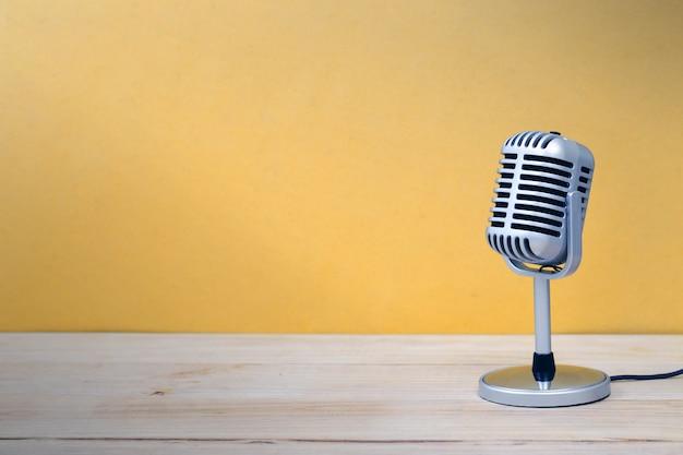 Uitstekende microfoon die op houten en gele achtergrond wordt geïsoleerd Premium Foto
