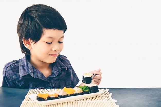 Uitstekende stijlfoto van aziatische mooie jongen eet sushi Gratis Foto
