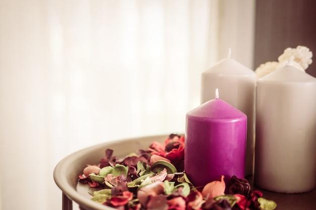 Uitstekende stijlfoto van decoratiekaarsen en bemerkte droge bloembloemblaadjes in een ruimte Gratis Foto