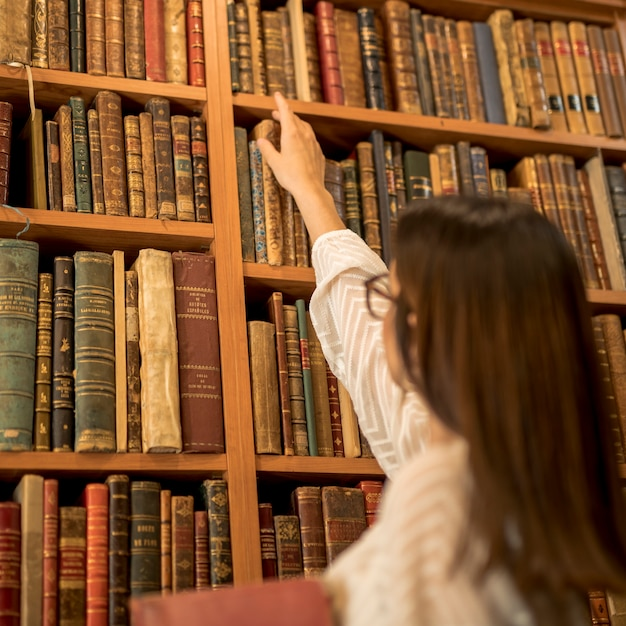 Uitstekende vrouwelijke student die uitstekend boek in bibliotheek kiest Gratis Foto
