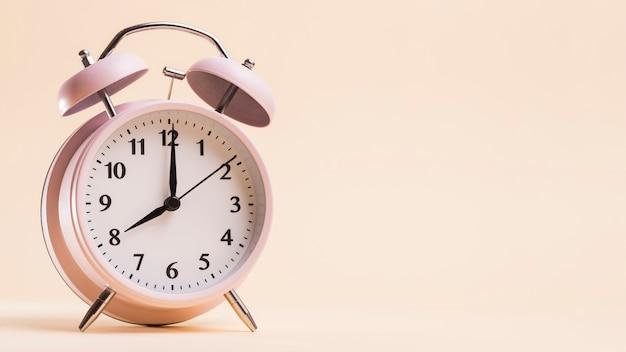 Uitstekende wekker die 8'kloktijd tegen beige achtergrond toont Gratis Foto