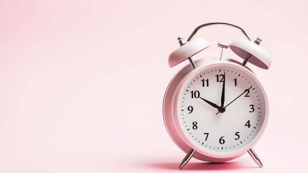 Uitstekende wekker tegen roze achtergrond Premium Foto
