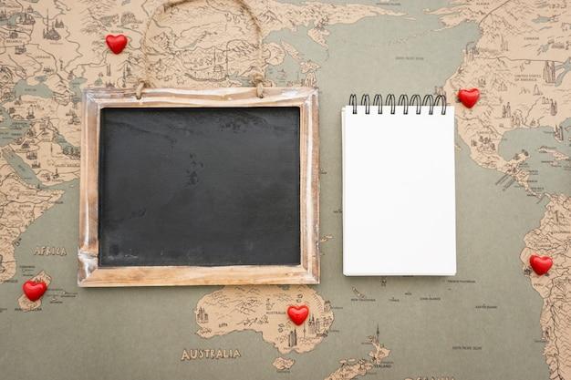 Uitstekende wereldkaart achtergrond met leisteen en notebook Gratis Foto