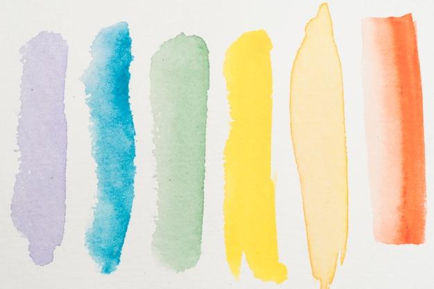 Uitstrijkjes van kleurrijke waterverf op papier Gratis Foto