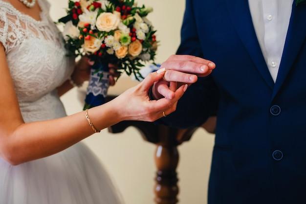 Uitwisseling van gouden ringen van de bruid en bruidegom op de bruiloft Premium Foto