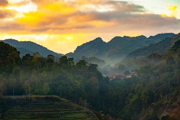 Uitzicht op de bergen, gele lucht en mist Premium Foto