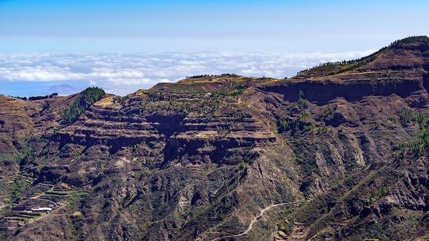 Uitzicht op de hoge bergen van het canarische eiland gran canaria met de wolken eronder aan de horizon. spanje. Premium Foto