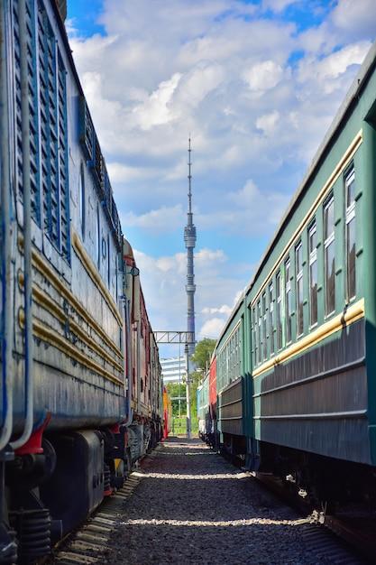 Uitzicht op de ostankino-toren tussen twee oude treinen Premium Foto