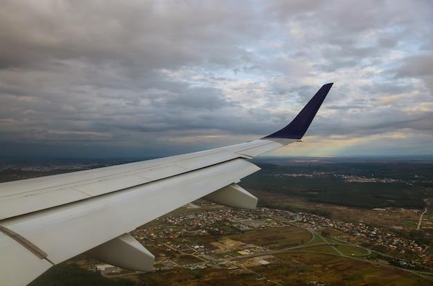Uitzicht op de stad vanuit een vliegend het vliegtuigvenster blauwe hemel, lichte wolken van vliegtuigvleugel Premium Foto