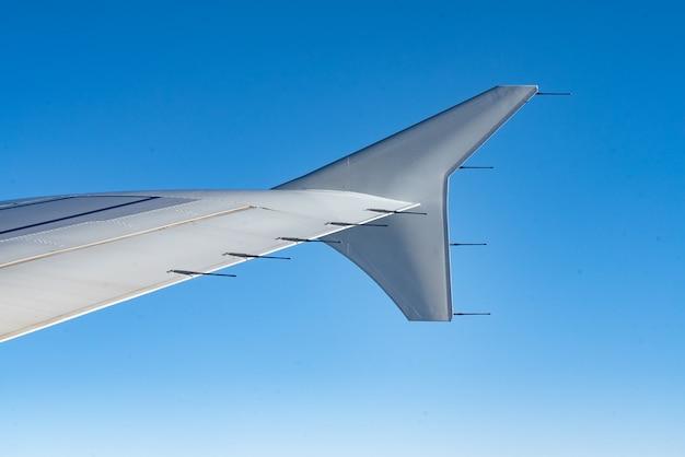 Uitzicht op de vleugel van het vliegtuig en de heldere blauwe lucht Premium Foto