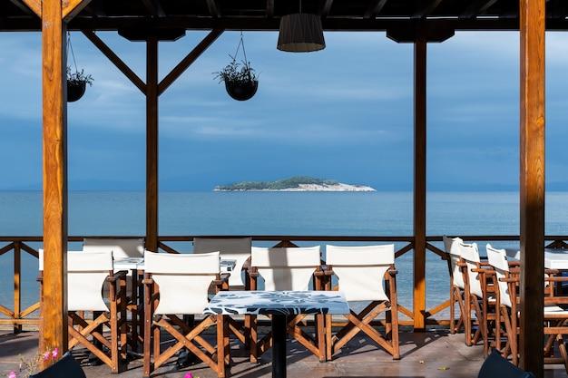 Uitzicht op een eiland en de egeïsche zee vanuit het lege restaurant Gratis Foto